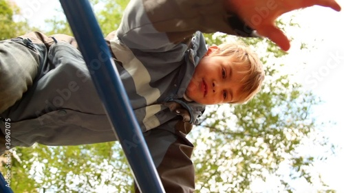 Boy climb on stairs at playground, view from below