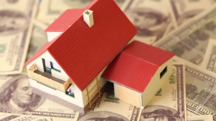 Toy house with tiled roof on dollars bank notes, rotates