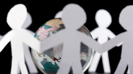 paper people stand and rotates around transparent globe