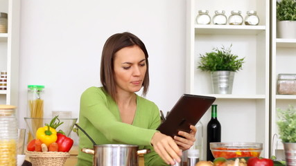 Woman in kitchen looking at recipe on tablet computer