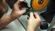 Man polishes piece of jewelry with grinding wheel