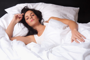 Attractive young woman is sleeping in her bed