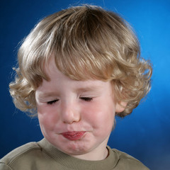 Kind mit blonden Locken schneidet Grimassen
