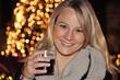 Junge Frau trinkt Glühwein auf Weihnachtsmarkt