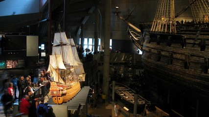 Tourists compare real and model ship inside museum, time lapse