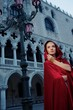 Beautifiul woman in red cloak against Dodge's Palace
