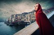 Beautifiul woman in red cloak on a bridge.