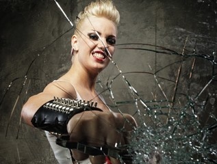 Punk girl breaking glass with a brass knuckles