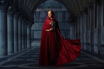 Beautifiul woman in red cloak outdoors