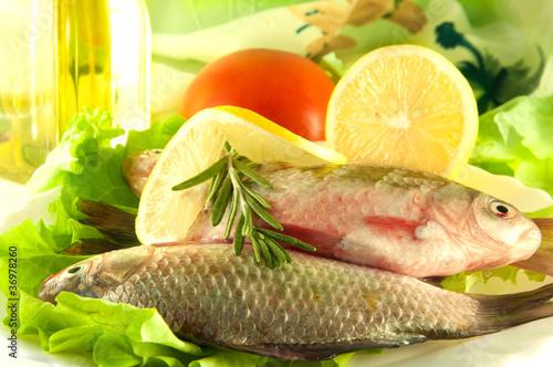 Leinwanddruck Bild Fresh fish, crucian with a lemon and an onions