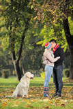 Boyfriend and girlfriend kissing in the park and a dog watching