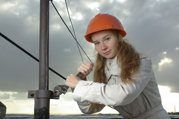Female with a wrench in an orange helmet