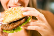 Frau im Restaurant isst Hamburger