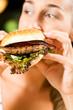rau im Restaurant isst Hamburger