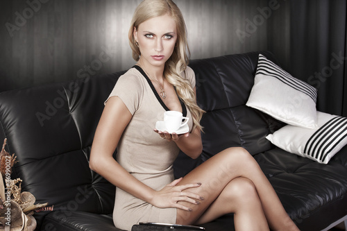 sitting on sofa drinking from a cup.she is straight and looks in