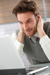 Cheerful man browsing internet smiling