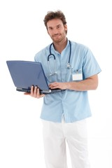 Handsome doctor with laptop smiling