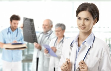 Mid-adult female doctor medical team in background