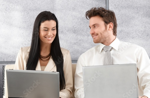 Elegant couple sitting on sofa using laptop