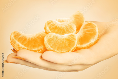 Tangerine slice. Hand with mandarin