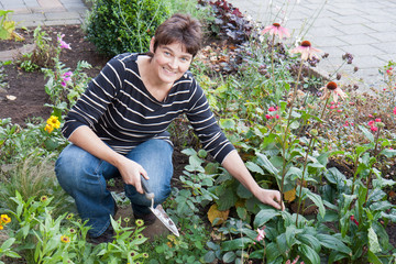 A woman is gardening in the front garden of her house
