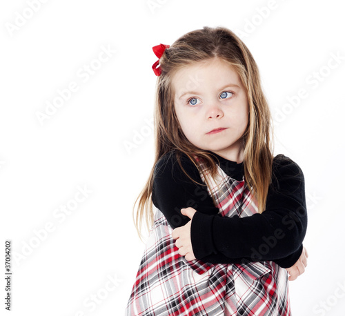 Young pretty girl in a dress on white background with arms folde