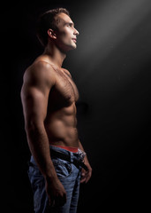 young muscular man on black background