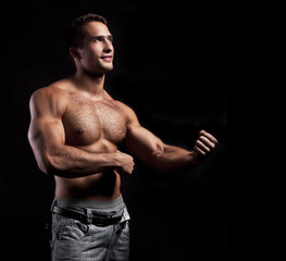 young muscular smiling man on black background