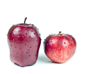 Two red appetizing apples with water drops isolated on the white