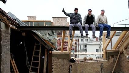 Triumphierende Arbeiter bei einem Dachausbau auf einer Traverse