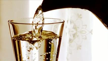 versare acqua in un bicchiere al tramonto