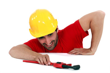 Man struggling to reach a pipe wrench