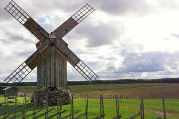 Wooden windmill against cloudy sky.