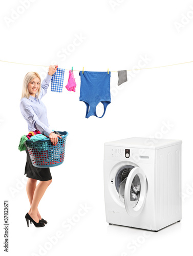 Young woman hanging clothes on clothes line next to a washing ma
