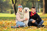 Smiling young man and woman hugging a labrador retreiver dog