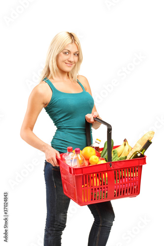 A young woman holding a shopping basket full with groceries