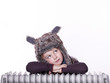 Sweet child with pelt cap rest on radiator