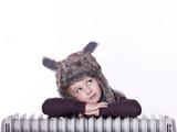 Sweet child with pelt cap rest on radiator poster
