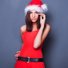 20-25 years od beautiful woman in christmas dress posing against