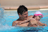 Father and daughter having fun in a swimming pool