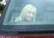 Woman in car, seen through windshield