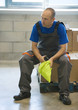 Factory worker sitting on cardboard box