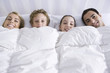 Family lying together in bed beneath comforter, smiling at camera