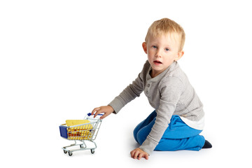 Kleinkind fährt mit Einkaufswaagen voller Gold