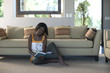 Young woman sitting on living room floor reading book