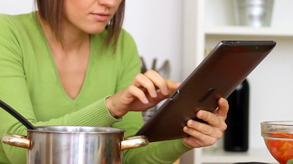 Woman cooking and looking at recipe on digital tablet
