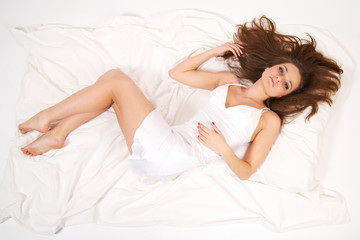 Beautiful young woman lying in bed