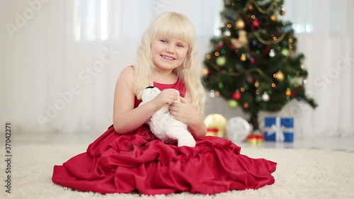 Happy child holding a teddy bear beside the Christmas tree