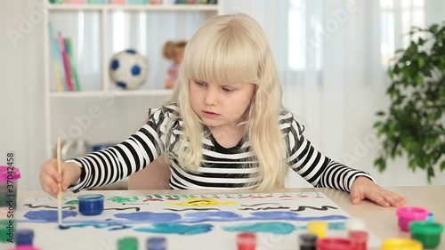 Little blonde girl paints pictures on a sheet of paper