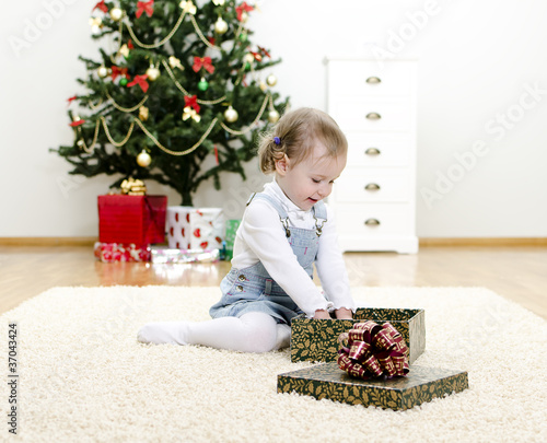 little girl unpacks the gift at Christmas